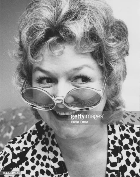 Portrait of actress Joan Sims wearing sunglasses and laughing August 1971