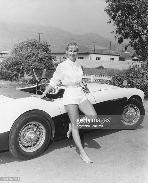 Portrait of actress Joanne Woodward standing next to her car in Hollywood November 1957