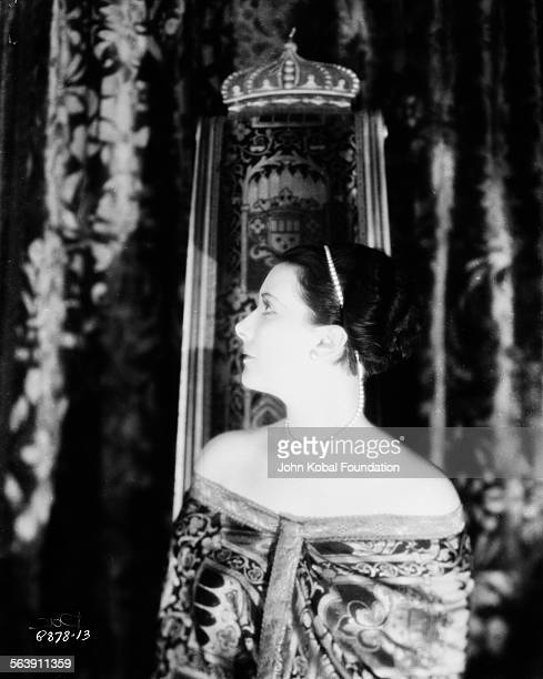 Portrait of actress Lil Dagover standing in front of an ornate curtain for Paramount Pictures 1927