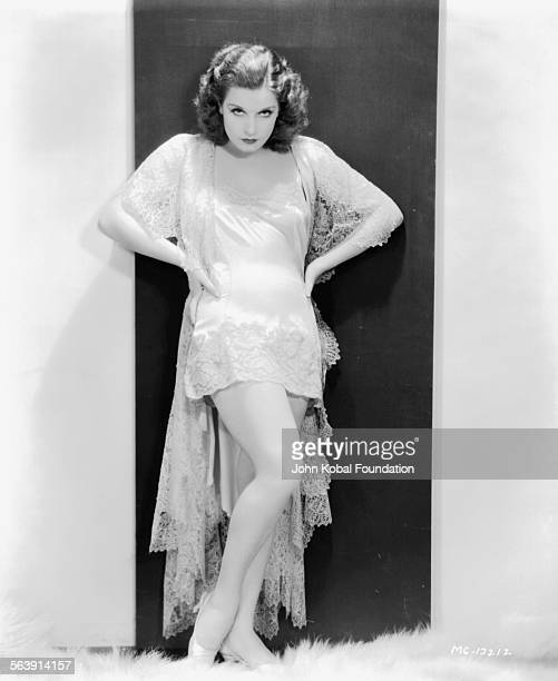 Portrait of actress Lili Damita wearing a lacetrimmed dress with a train for MGM Studios 1930