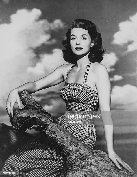 Portrait of actress Lilli Palmer sitting on a branch wearing a gingham dress circa 1950