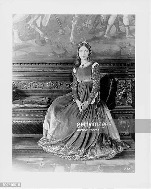 Portrait of actress Lillian Gish wearing a medieval dress and sitting on an ornate bench circa 19101920