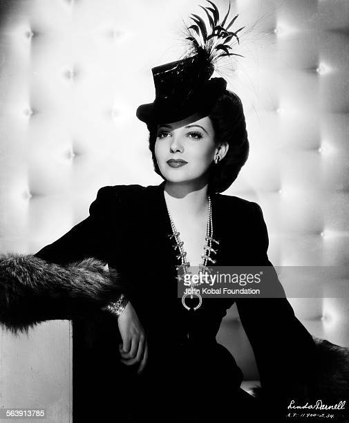 Portrait of actress Linda Darnell wearing furtrimmed dress and feathered hat for 20th Century Fox circa 1950