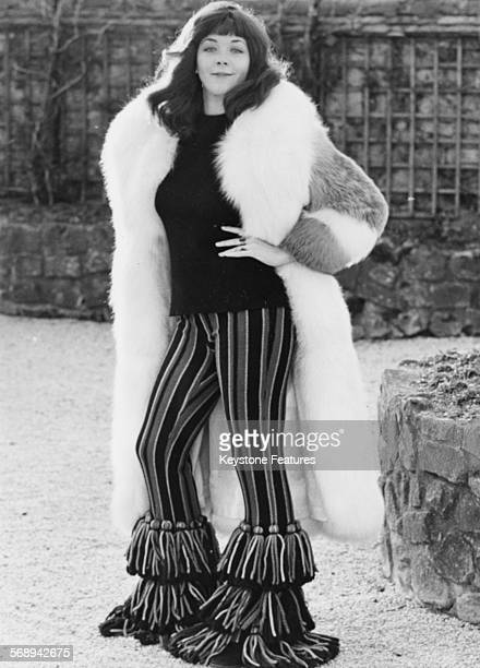 Portrait of actress Linda Thorson modeling striped Dior bell bottom trousers and a fur coat Paris circa 1975