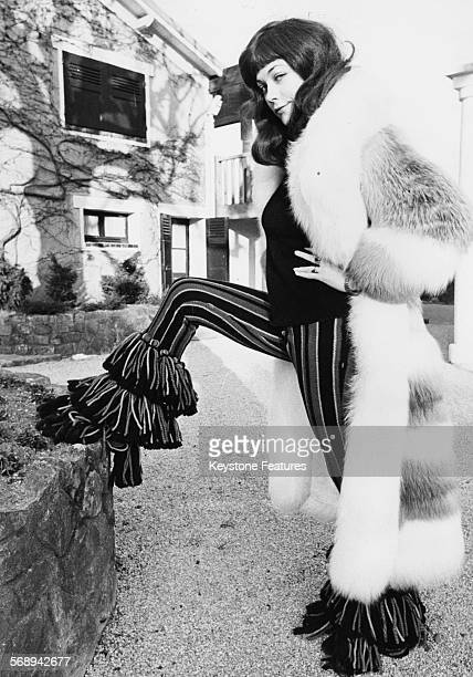 Portrait of actress Linda Thorson modeling striped Dior bell bottom trousers and a fur coat outside L'Hotellerie du Bas Breau Paris circa 1975