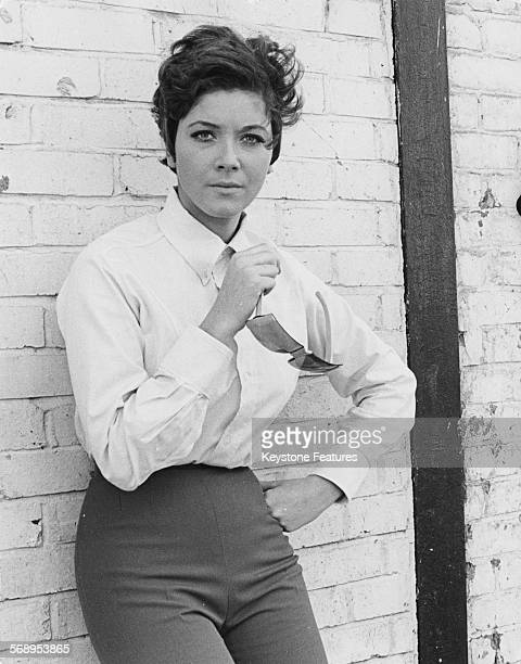 Portrait of actress Linda Thorson star of 'The Avengers' television series leaning against a wall wearing a tailored shirt and trousers circa 1967