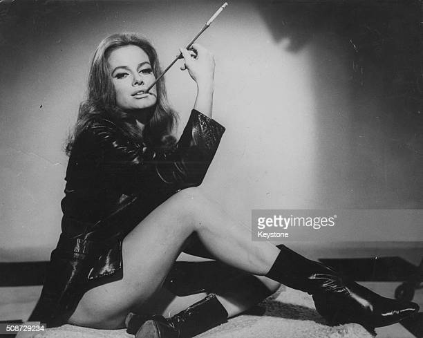 Portrait of actress Luciana Paluzzi, star of the James Bond film 'Thunderball', wearing nothing but a leather jacket and boots as she smokes a...
