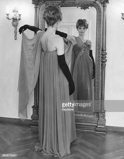 Portrait of actress Maria Perschy inspecting herself in a mirror wearing a gown and long gloves at a fashion house in Rome May 24th 1962