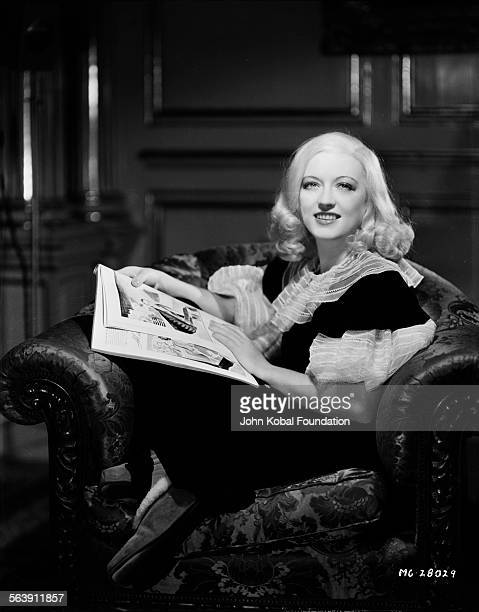 Portrait of actress Marion Davies curled up in an armchair reading a book for MGM Studios November 7th 1932