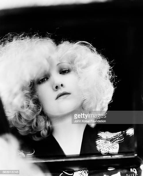 Portrait of actress Marion Davies photographed through a mirror on her lap for MGM Studios May 18th 1930
