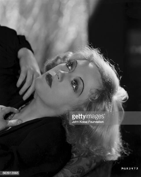Portrait of actress Marion Davies reclining back on a couch for MGM Studios April 23rd 1932