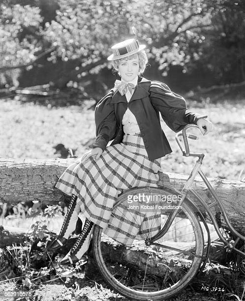 Portrait of actress Marion Davies sitting on a large tree branch with her bicycle next to her for MGM Studios April 12th 1930