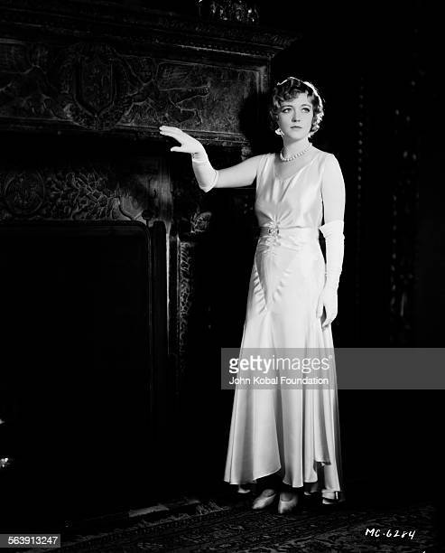 Portrait of actress Marion Davies standing next to a fireplace for MGM Studios May 16th 1930