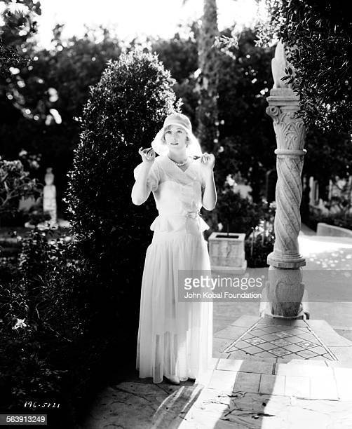 Portrait of actress Marion Davies standing outdoors in a garden for MGM Studios May 17th 1930