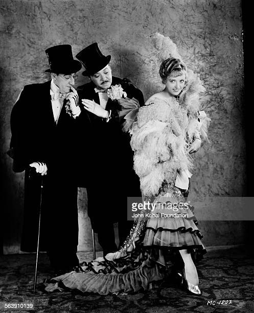Portrait of actress Marion Davies wearing a feather shawl and headdress being admired by two men in top hats for MGM Studios February 5th 1930