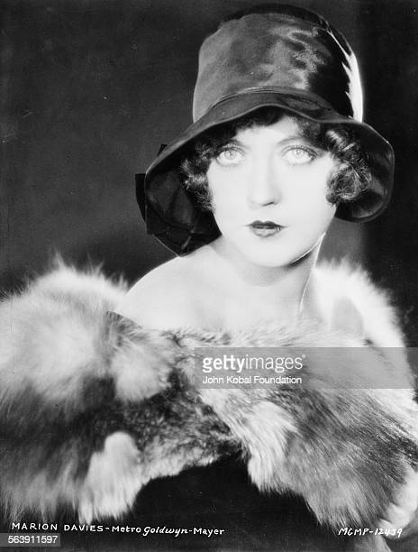 Portrait of actress Marion Davies wearing a fur stole and hat for MGM Studios 1931
