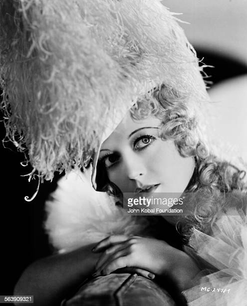 Portrait of actress Marion Davies wearing a large feather headdress for MGM Studios July 9th 1932