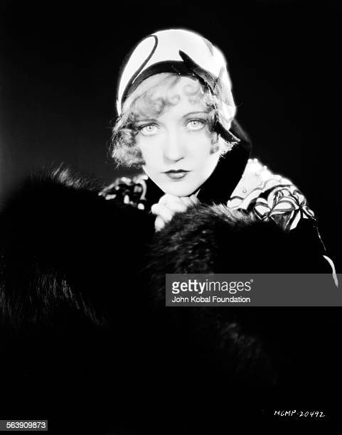 Portrait of actress Marion Davies wearing a small hat and fur cuffs for MGM Studios 1930