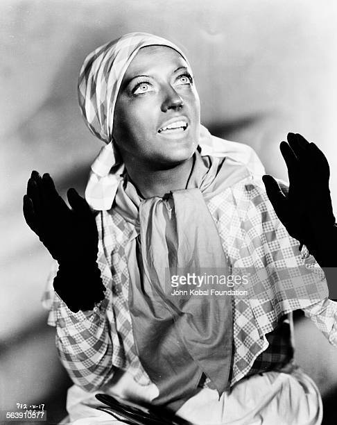Portrait of actress Marion Davies wearing gloves and a head scarf with a dirty face as she appears in the film 'Operator 13' for MGM Studios...