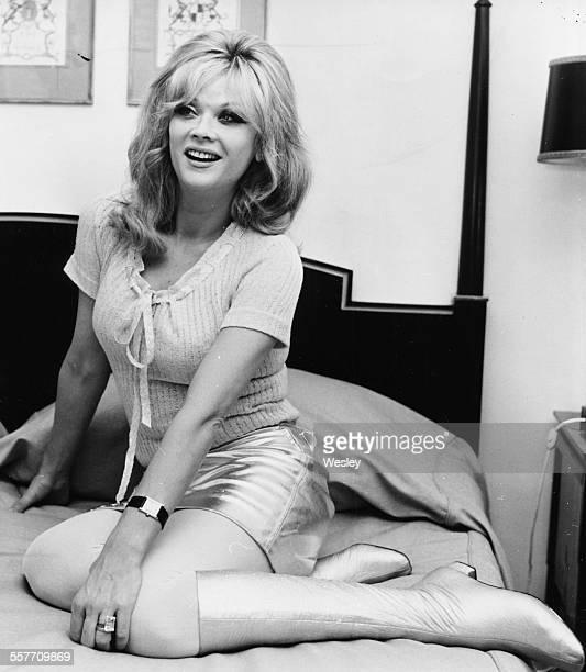 Portrait of actress Monique van Vooren on the bed in her hotel room London March 1st 1967