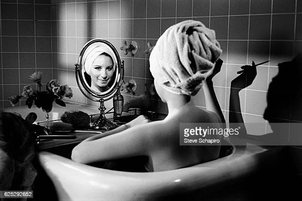 Portrait of actress & musician Barbra Streisand as she sits, her back to the camera, in a bathtub and smiles into a small mirror, Beverly Hills,...