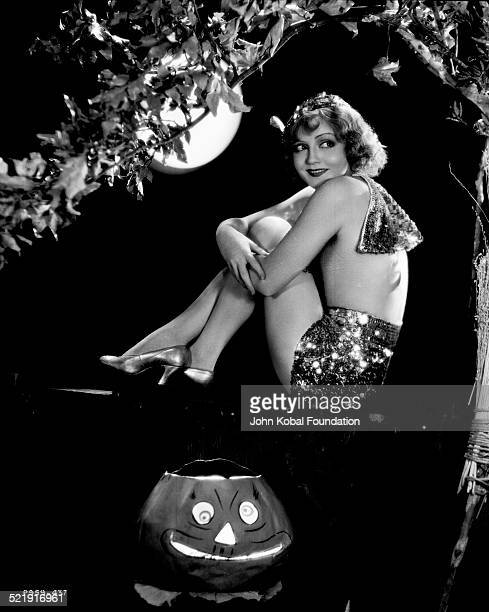 Portrait of actress Nancy Carroll sitting in a tree next to a jacko'lantern wearing sparkled shorts for Paramount Pictures 1929