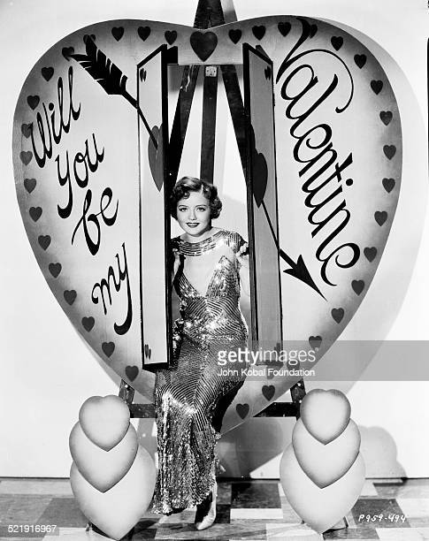 Portrait of actress Nancy Carroll sitting inside a prop heart labeled 'Will You Be My Valentine' for Paramount Pictures 1929