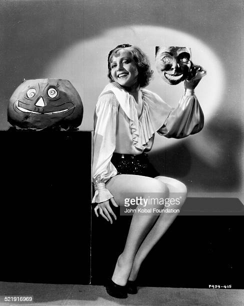 Portrait of actress Nancy Carroll sitting next to a jacko'lantern wearing shorts and a ruffled blouse and holding up a mask for Paramount Pictures...