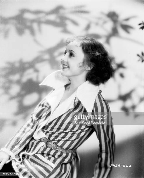 Portrait of actress Nancy Carroll wearing a shirt and striped jacket for Paramount Pictures 1928
