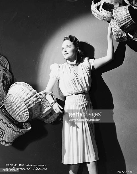 Portrait of actress Olivia de Havilland holding lots of wicker baskets in both hands for Paramount Pictures 1946