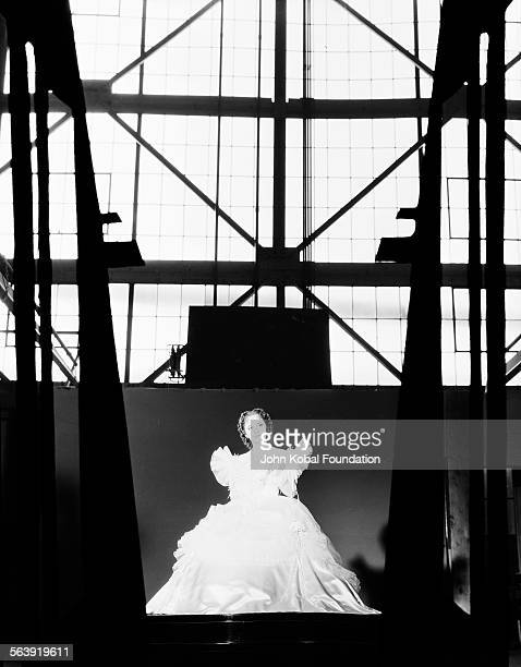 Portrait of actress Olivia de Havilland pictured far away from the camera across a film set for Warner Bros Studios 1939