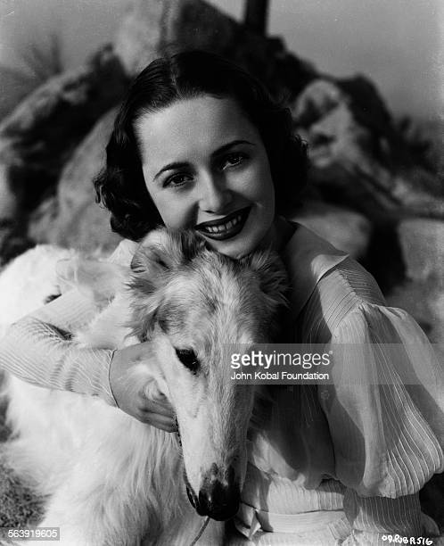 Portrait of actress Olivia de Havilland posing with a pet dog for Warner Bros Studios 1937