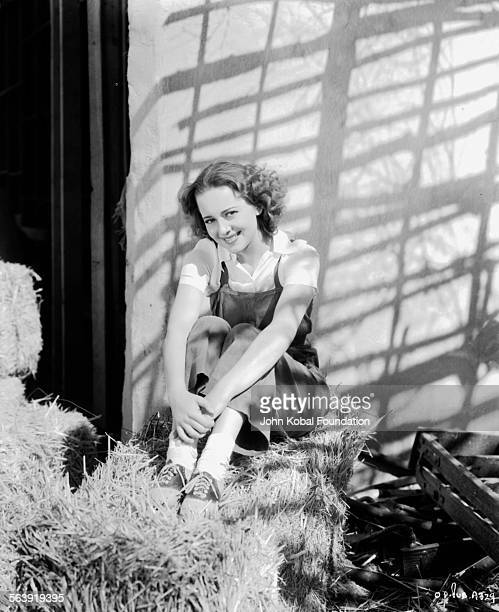 Portrait of actress Olivia de Havilland sitting in a barn wearing dungarees for Warner Bros Studios 1935