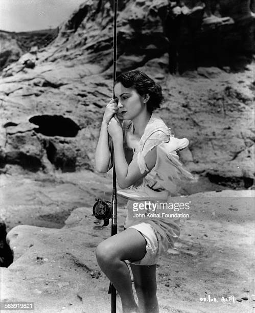 Portrait of actress Olivia de Havilland standing next to the sea holding a fishing rod as she appears in the film 'Captain Blood' for Warner Bros...