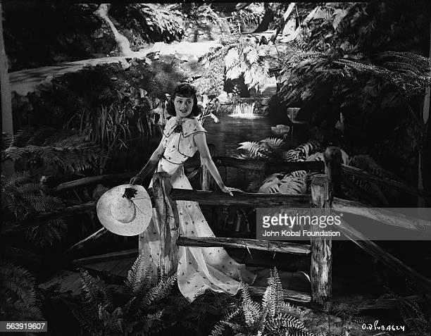 Portrait of actress Olivia de Havilland standing on a bridge in a woodland clearing for Warner Bros Studios 1937