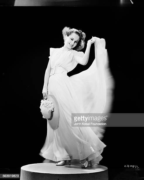 Portrait of actress Olivia de Havilland waving her skirt in the air for Warner Bros Studios 1938