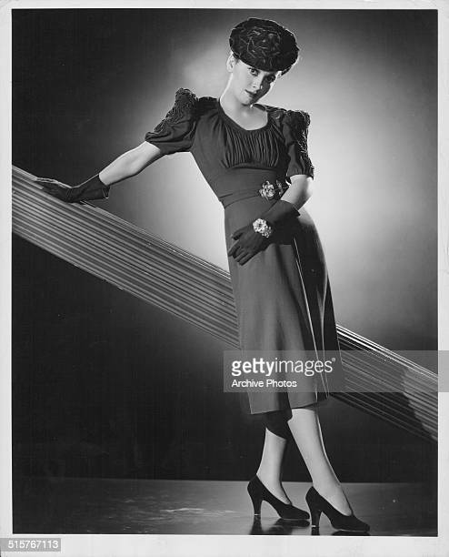 Portrait of actress Olivia de Havilland wearing a crepe cocktail dress and hat circa 1939