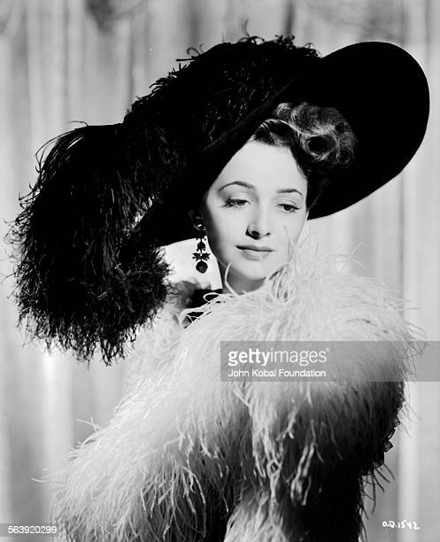 Portrait of actress Olivia de Havilland wearing a fur outfit and a large hat for Warner Bros Studios 1938