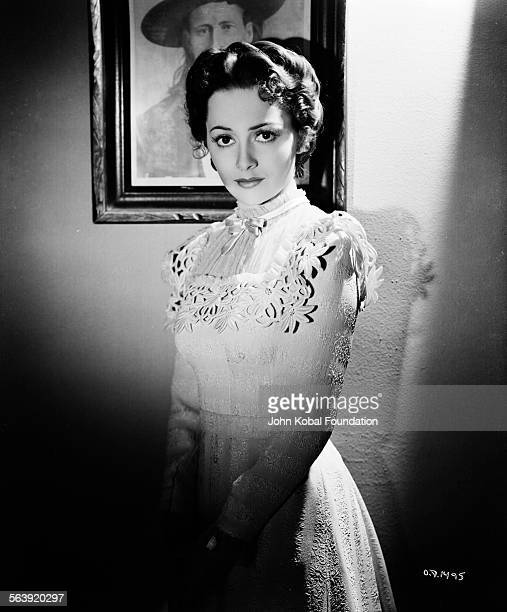 Portrait of actress Olivia de Havilland wearing a highnecked dress with a bow for Warner Bros Studios 1938