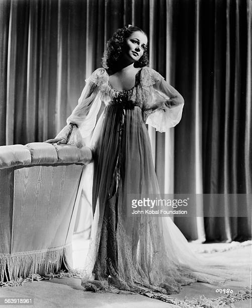 Portrait of actress Olivia de Havilland wearing a layered chiffon gown as she appears in the film 'The Great Garrick' for Warner Bros Studios 1937