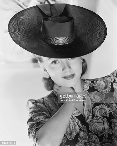 Portrait of actress Olivia de Havilland wearing a patterned dress and widebrimmed hat for Warner Bros Studios 1938