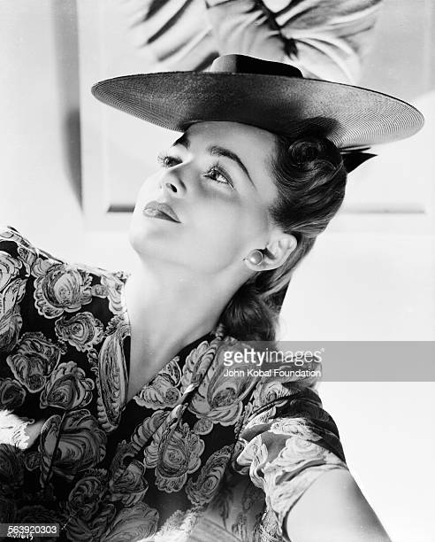 Portrait of actress Olivia de Havilland wearing a patterned dress and a hat for Warner Bros Studios 1939