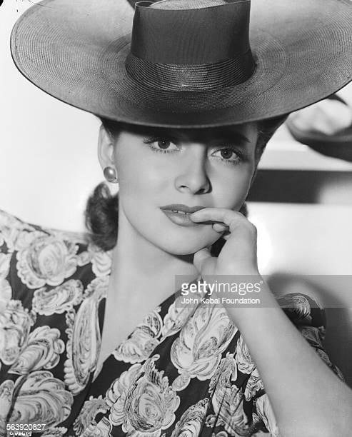 Portrait of actress Olivia de Havilland wearing a patterned dress and a hat for Warner Bros Studios 1939