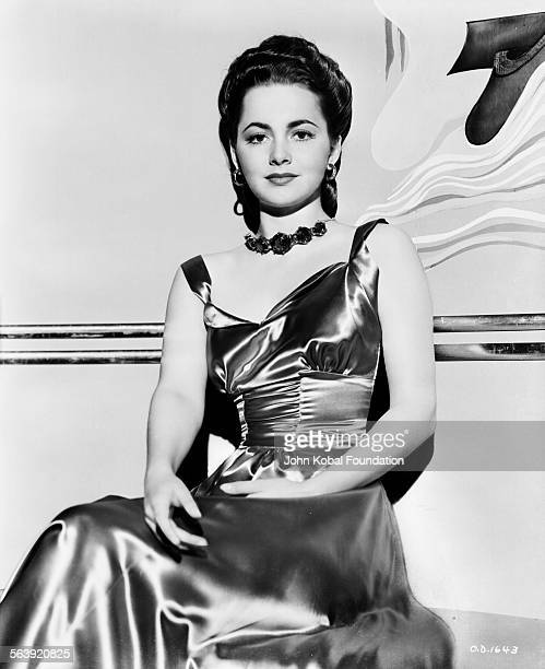 Portrait of actress Olivia de Havilland wearing a satin dress for Warner Bros Studios 1939