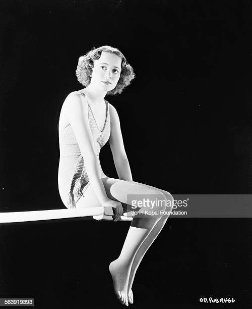 Portrait of actress Olivia de Havilland wearing a swimsuit and sitting on the end of a diving board for Warner Bros Studios 1937