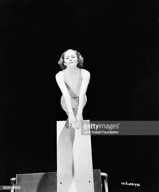Portrait of actress Olivia de Havilland wearing a swimsuit and standing on the end of a diving board for Warner Bros Studios 1937