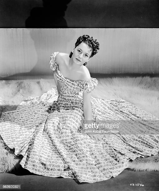 Portrait of actress Olivia de Havilland with her patterned dress fanned out around her for Warner Bros Studios 1938