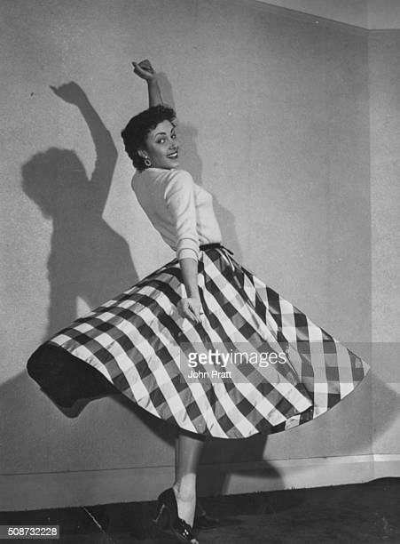 Portrait of actress Pascale Roberts dancing as he check skirt fans out around her circa 1965