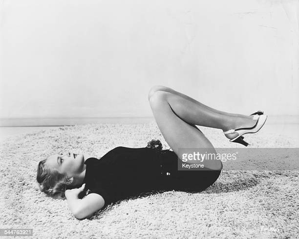 Portrait of actress Patrice Wymore lying on a beach on her back with her knees pulled up to her chest as she gets in shape for her role in the movie...