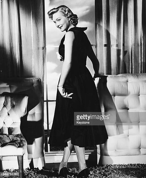 Portrait of actress Patrice Wymore wearing a swing dress and stockings with her back to the camera circa 1955